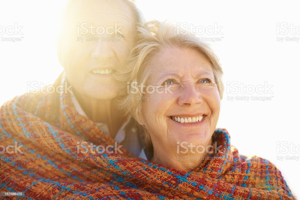 Cute old couple smiling wrapped in a shawl royalty-free stock photo