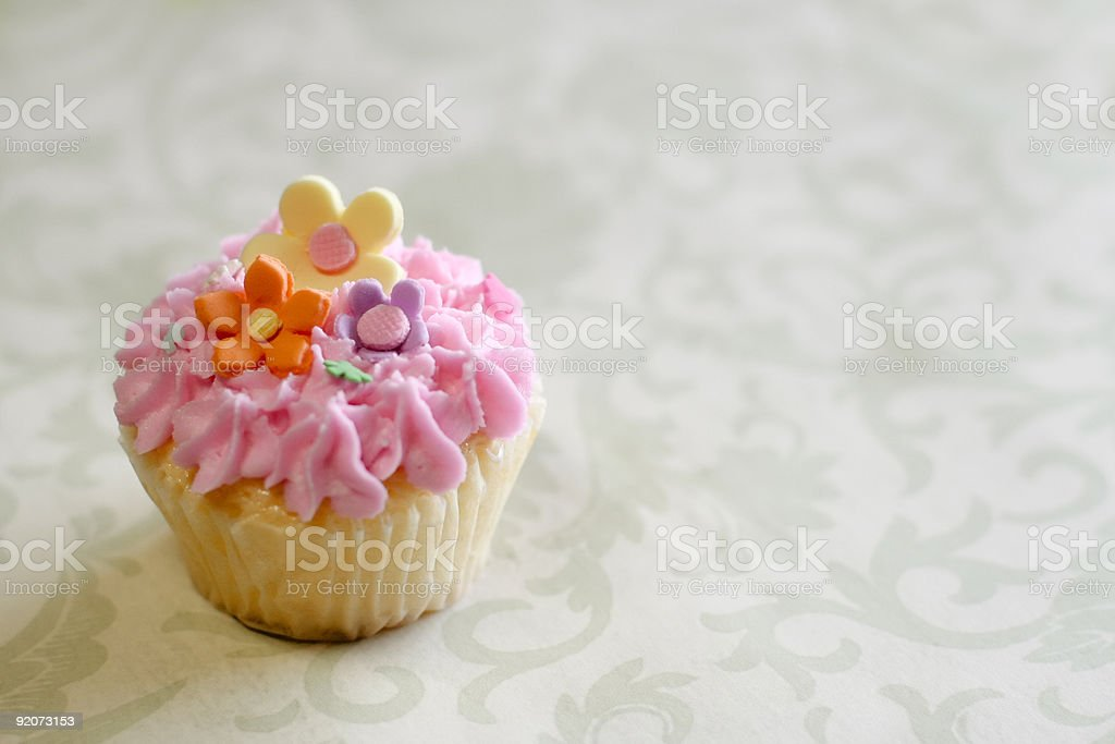 Cute pastel-colored cupcake topped with gumpaste flowers; pink icing. royalty-free stock photo