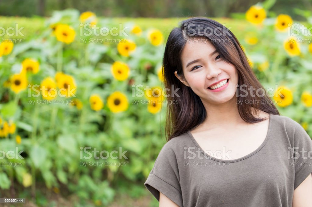 cute portrait asian Thai teen smile with sunflower with copy space. stock photo