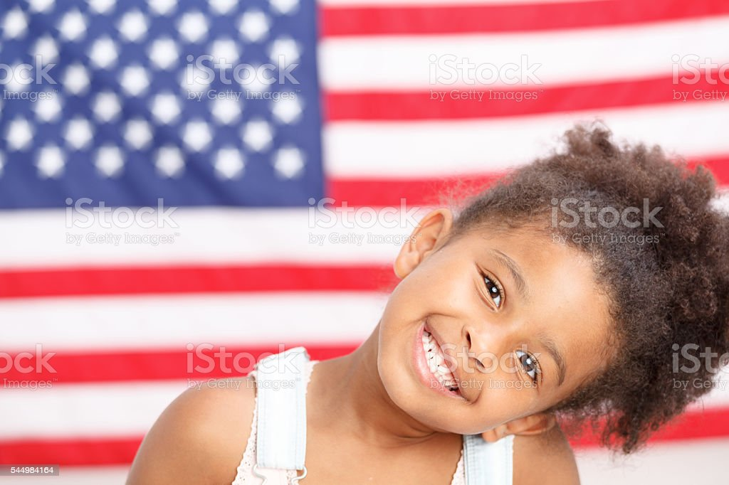Cute preschool girl smiling in front of USA flag stock photo