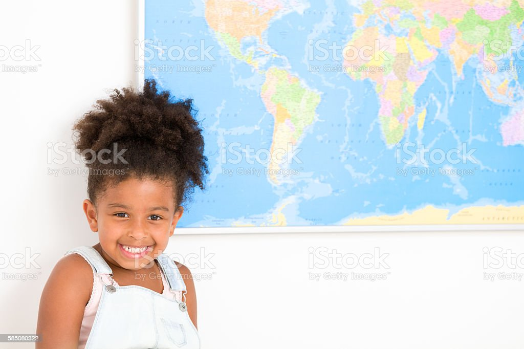 Cute preschool girl with world map stock photo