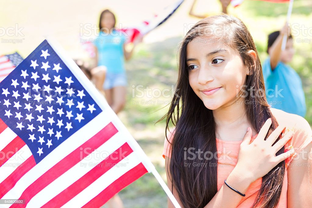 Cute preteen Hispanic girl with American flag at parade stock photo