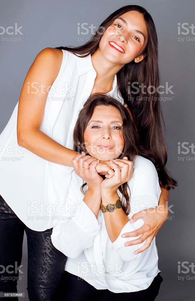 cute pretty teen daughter with mature mothr hugging, fashion style stock photo