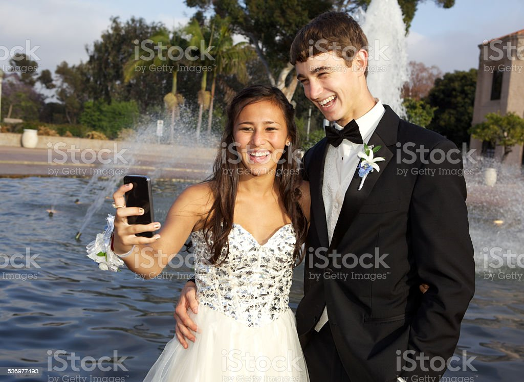 Cute Prom Couple Taking a Selfie in front of  Fountain stock photo