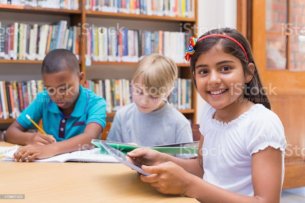 Cute pupil using tablet computer in library stock photo