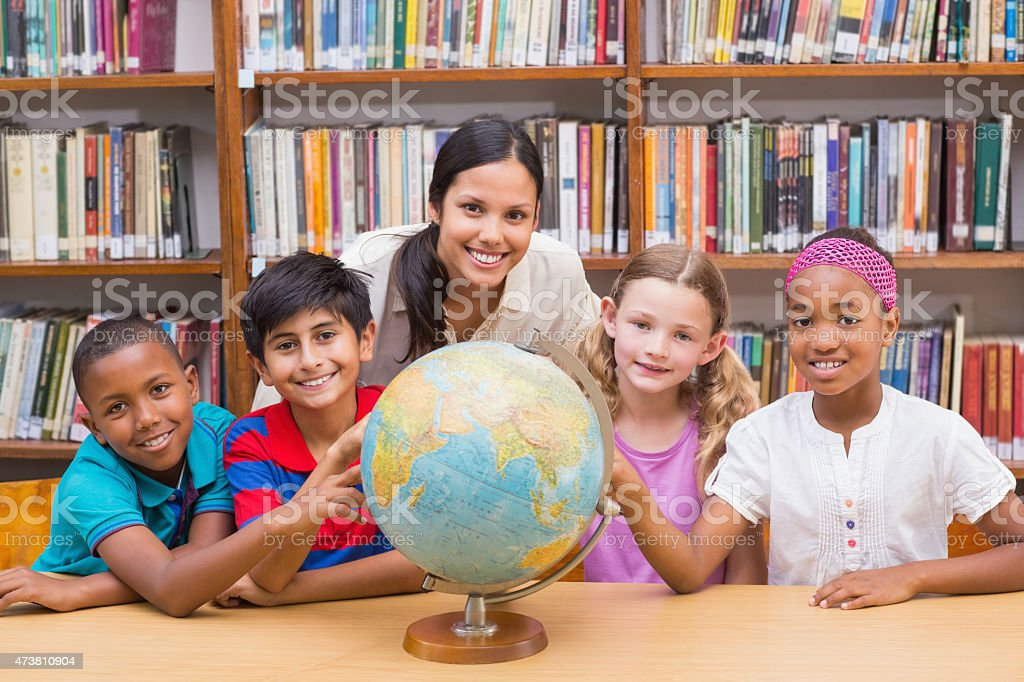 Cute pupils and teacher looking at globe in library stock photo