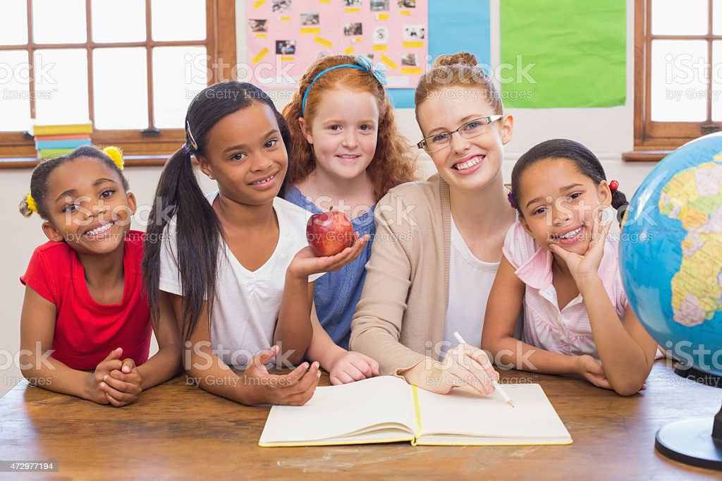 Cute pupils and teacher smiling at camera in classroom stock photo