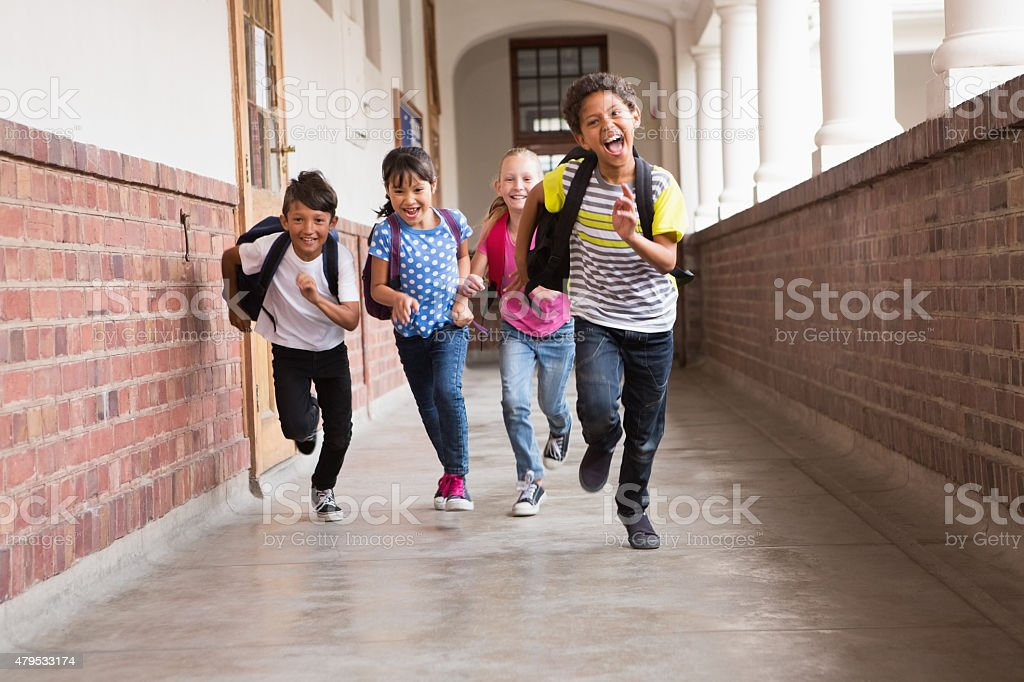Cute pupils running down the hall stock photo