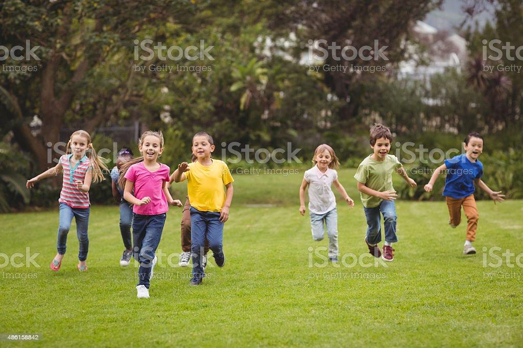 Cute pupils running towards camera stock photo