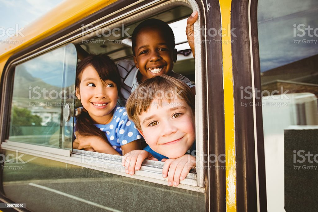 Cute pupils smiling at camera in the school bus stock photo