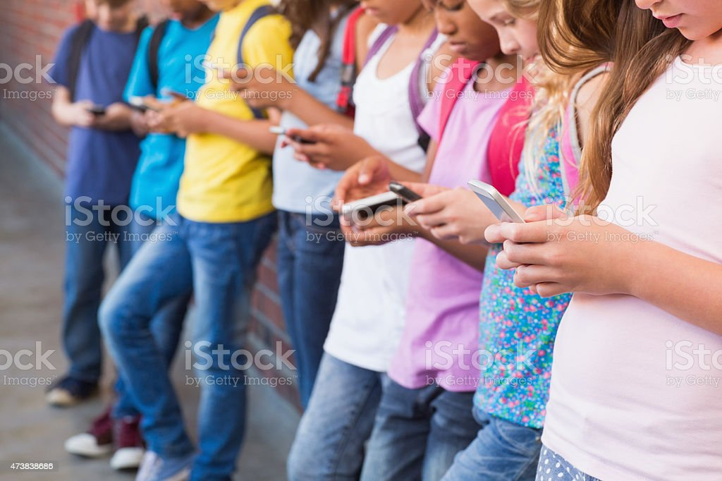 Cute pupils using mobile phone stock photo