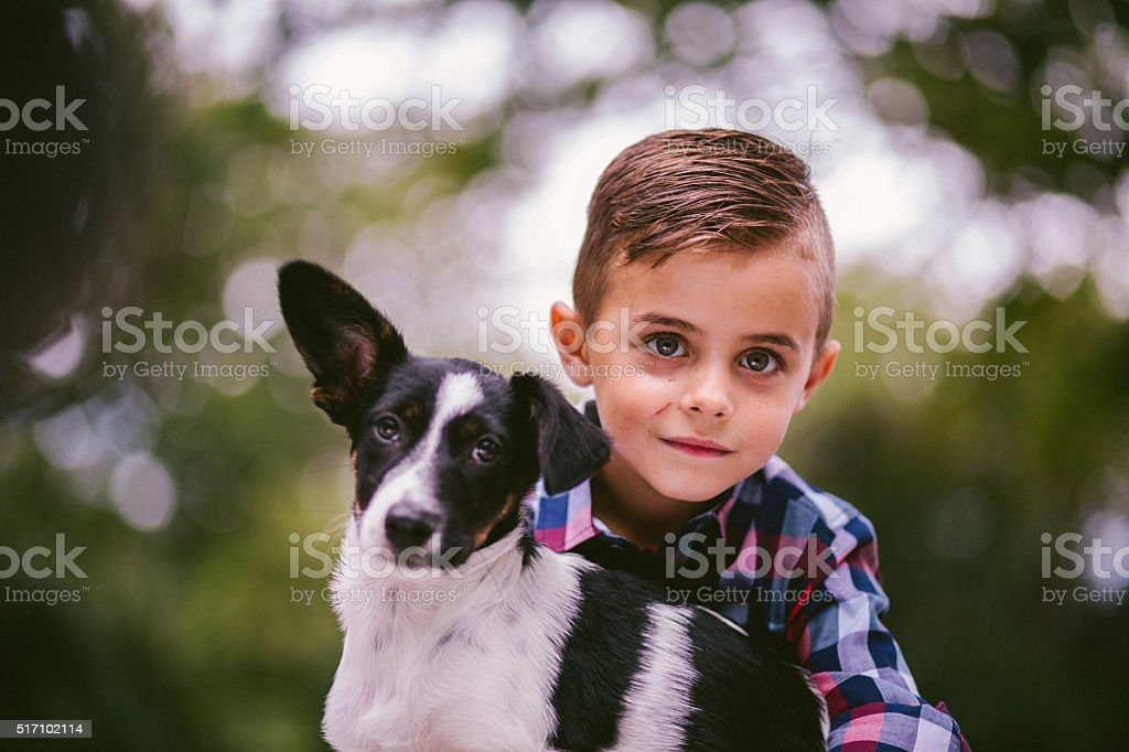 Cute puppy and mischievous boy looking at camera in nature stock photo