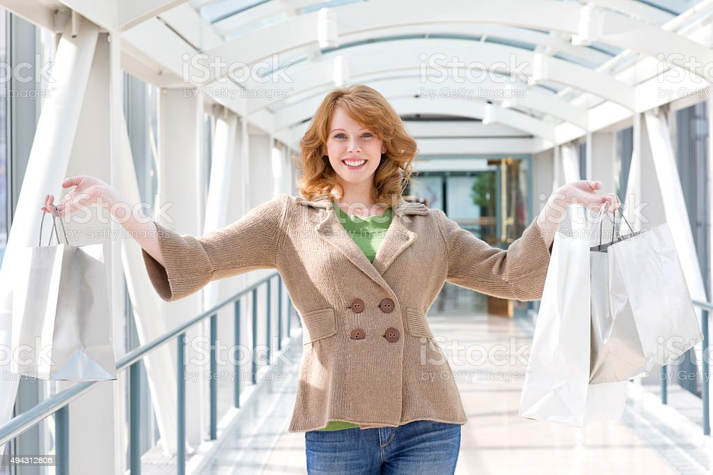 Cute Red Head Holding Shopping Bags In Airport stock photo