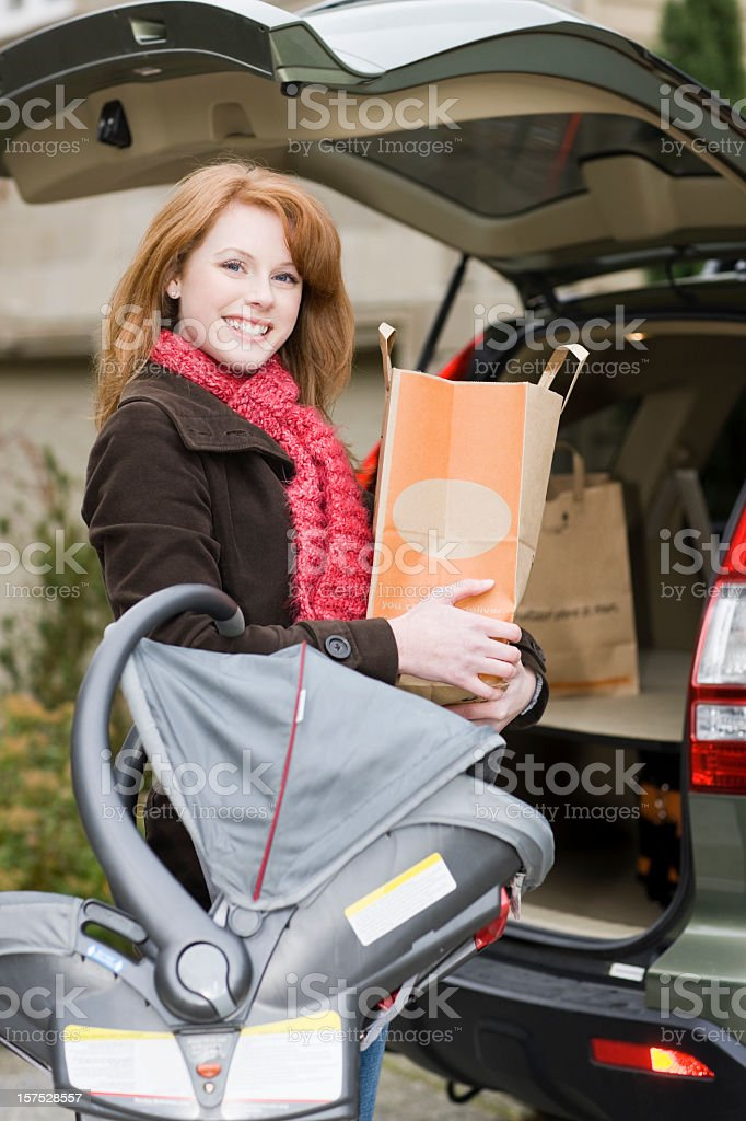 Beautiful Smiling Young Woman with Shopping Groceries and Car Seat stock photo