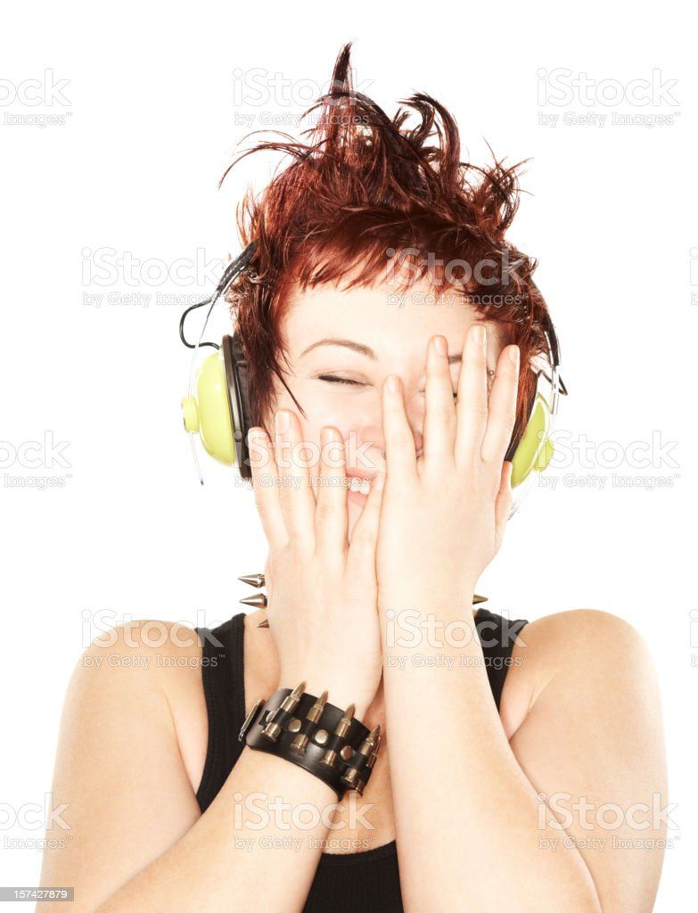 Cute redhead laughing while listening to music stock photo