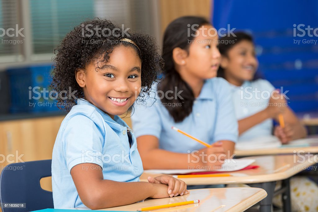 Cute schoolgirl smiles at the camera in classroom stock photo