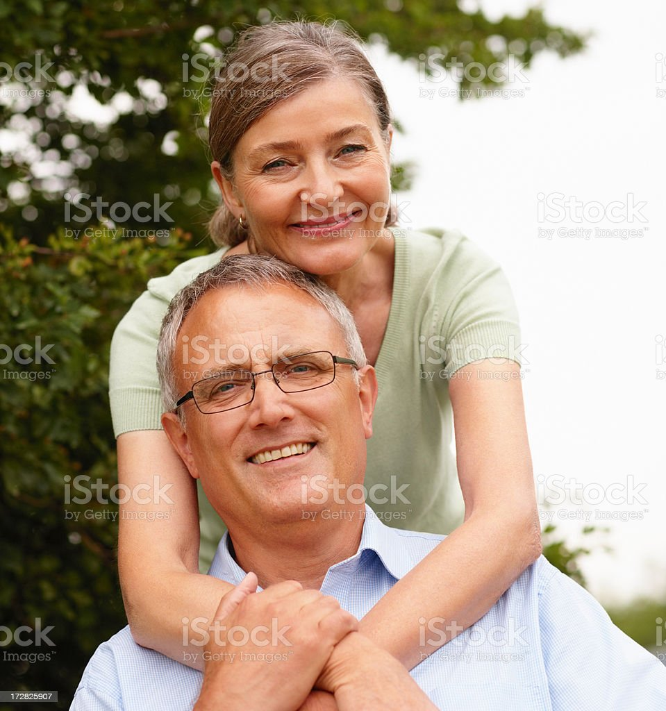 Cute senior woman with arms around husband stock photo