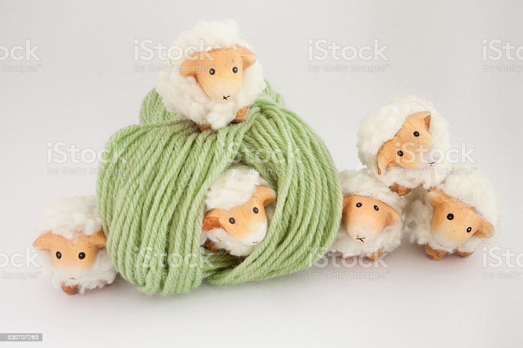 Cute sheep playing together with a ball of green wool stock photo