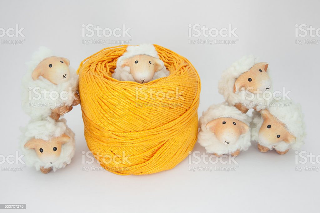 Cute sheep playing together with a ball of yellow wool stock photo