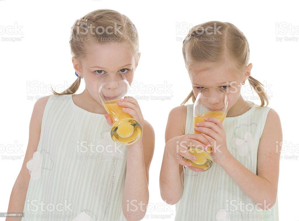 Mignon sisters boisson dans un verre de jus d'orange frais. photo libre de droits