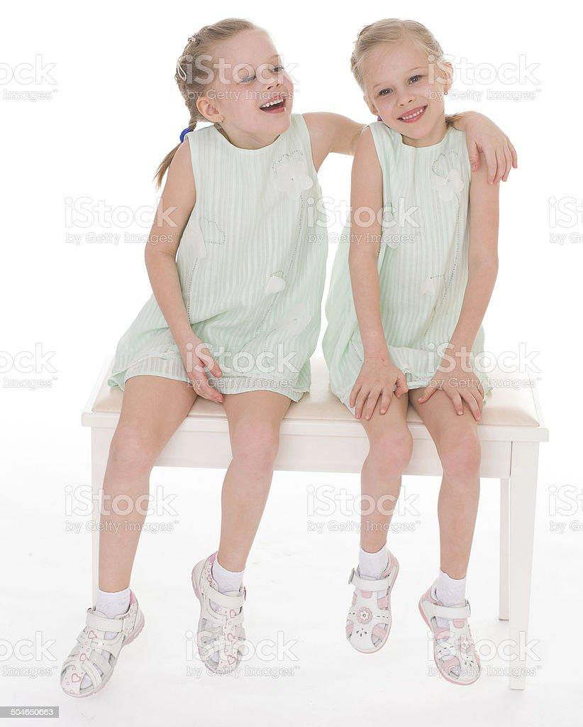 Mignon sœurs s'amuser assis sur une chaise. photo libre de droits