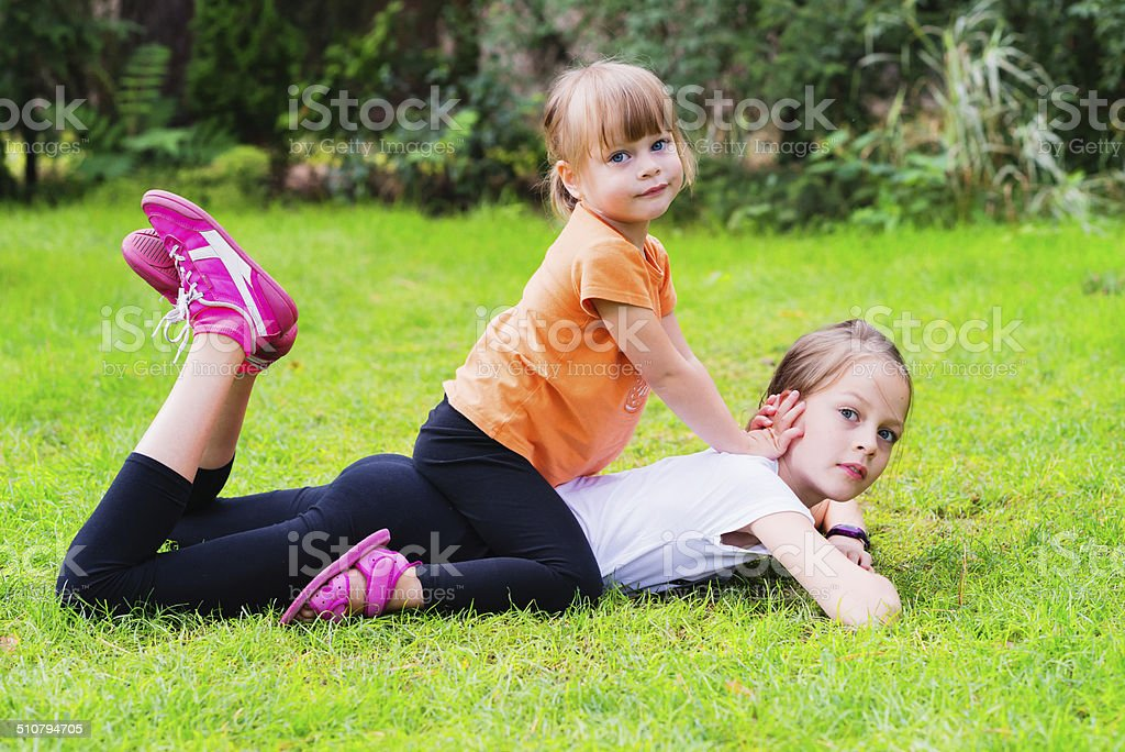 Cute sisters lying on the grass stock photo