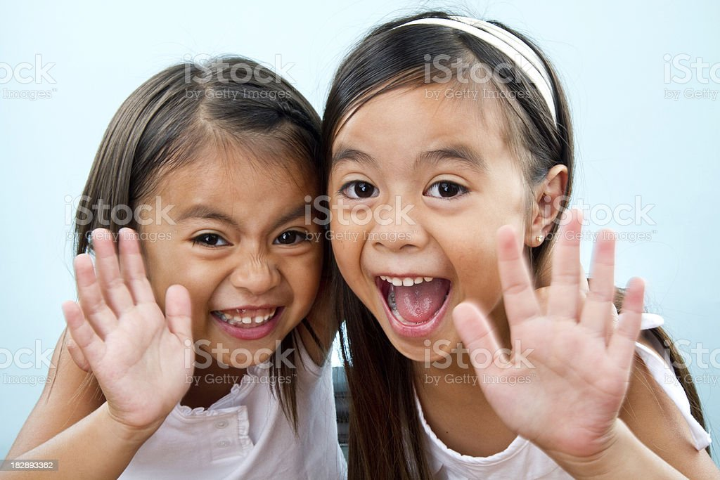 cute sisters waving hi at camera stock photo