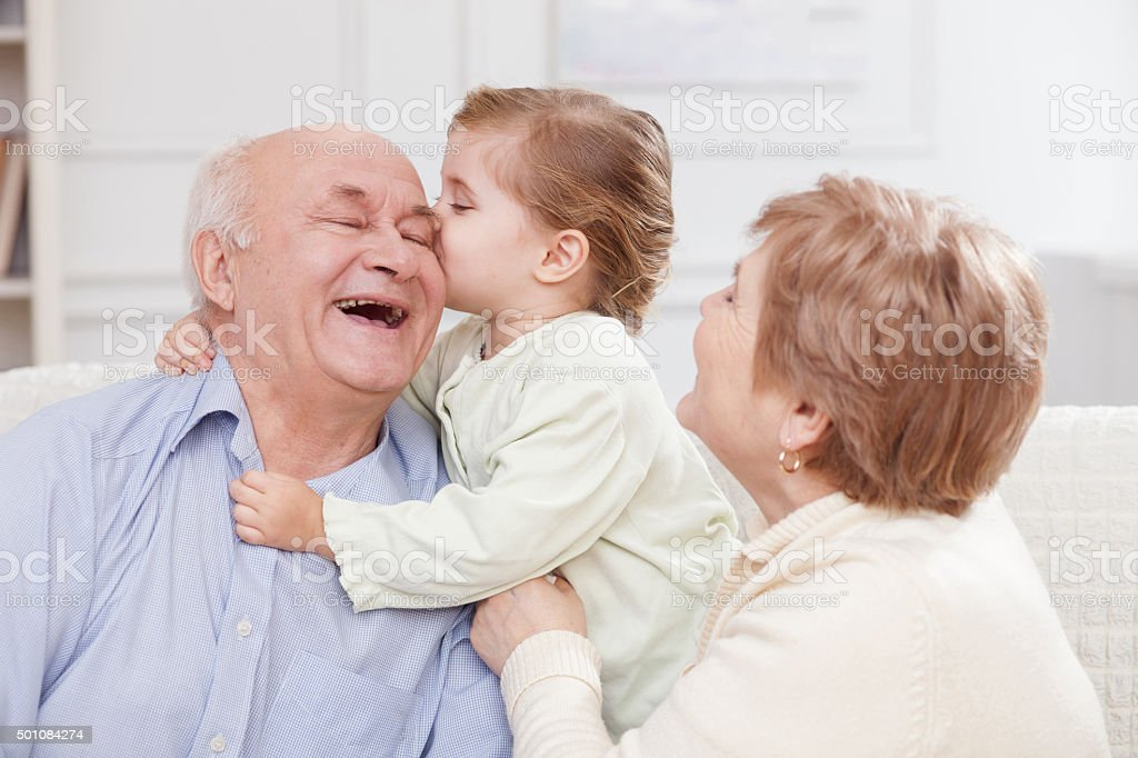 Cute small child is expressing love to grandparents stock photo