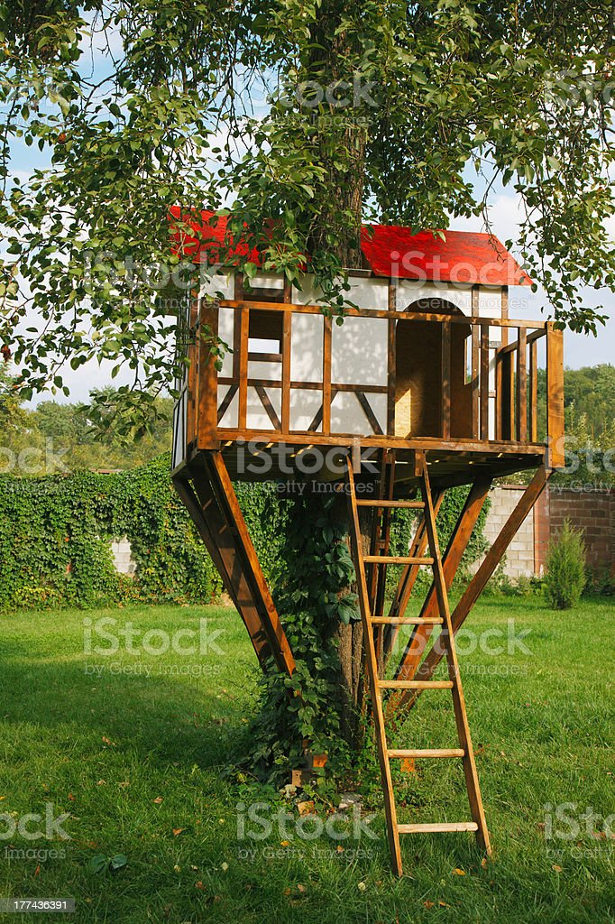 Cute small tree house for kids on backyard. stock photo