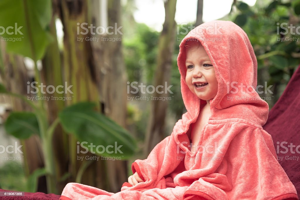 Cute smiling baby covered with pink blanket sitting on sunbed stock photo