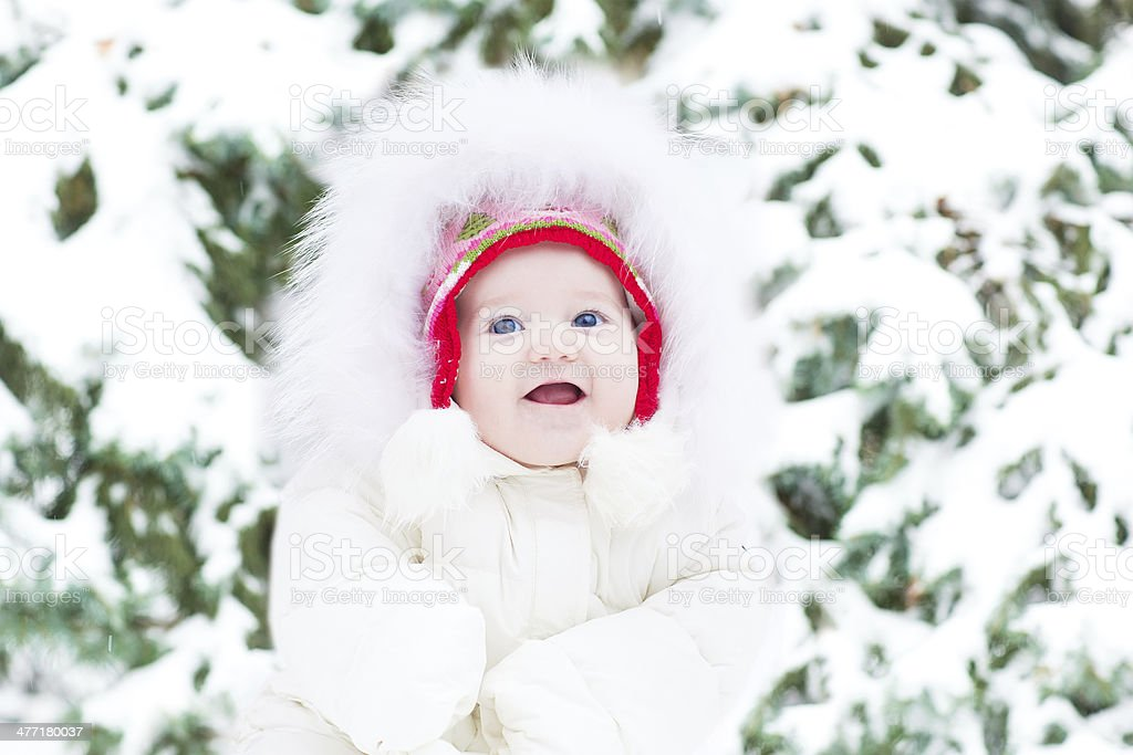 Cute smiling baby girl sitting next to Christmas tree royalty-free stock photo