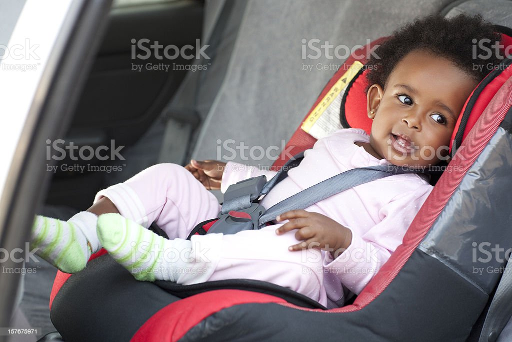 Cute smiling baby strapped in a car seat for safety stock photo