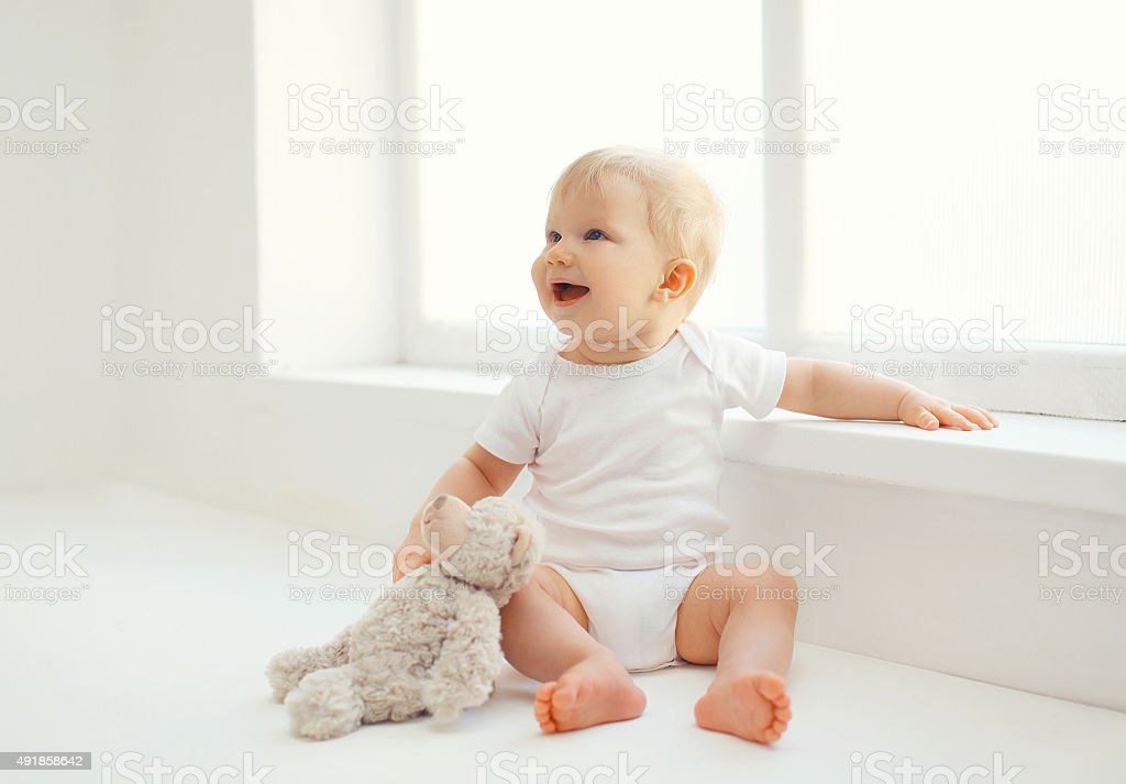 Cute smiling baby with teddy bear toy home in room stock photo
