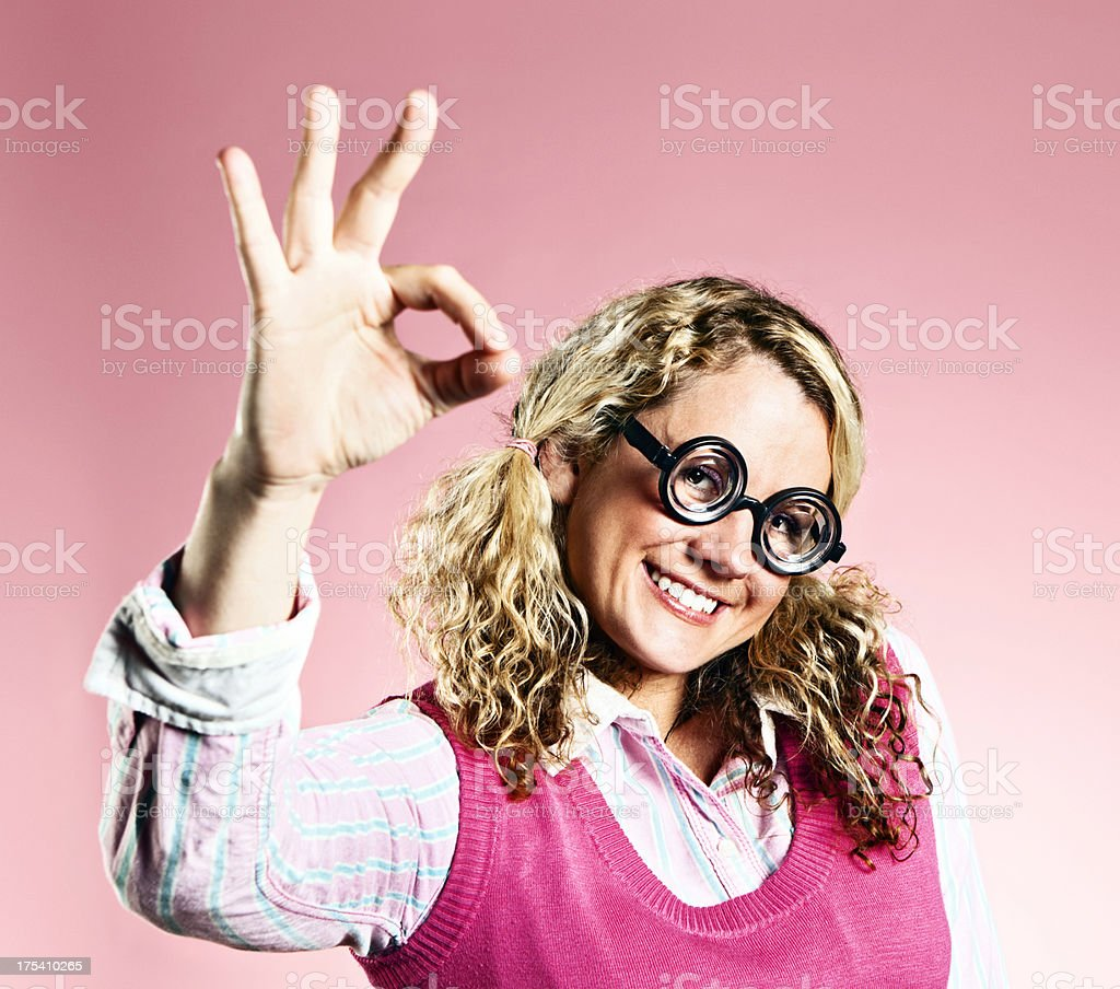 Cute smiling blonde nerd makes OK hand sign royalty-free stock photo