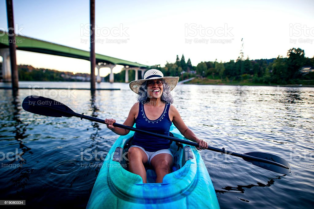 Cute smiling elderly woman wearing a hat and kayaking stock photo