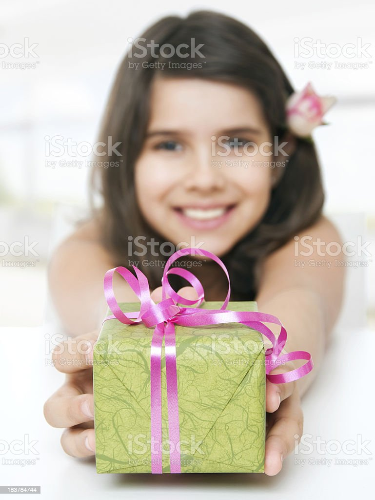 Cute smiling girl holding a gift. stock photo