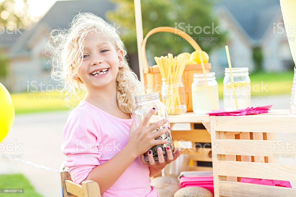 Cute smiling girl holding up her earnings from selling lemonade stock photo