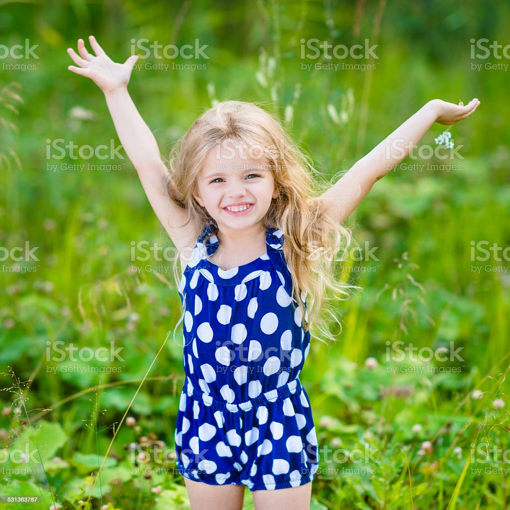 Cute smiling little girl with blond hair and raised hands stock photo