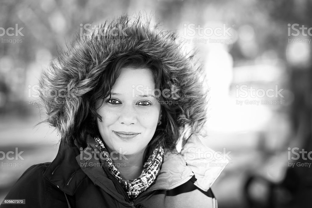 Cute smiling winter girl outdoors with faux fur hood up stock photo