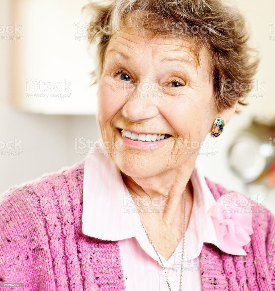 Cute, smiling woman in her 80s is happily surprised stock photo