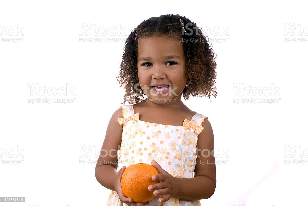 Cute smiling young girl in a dress holding an orange stock photo