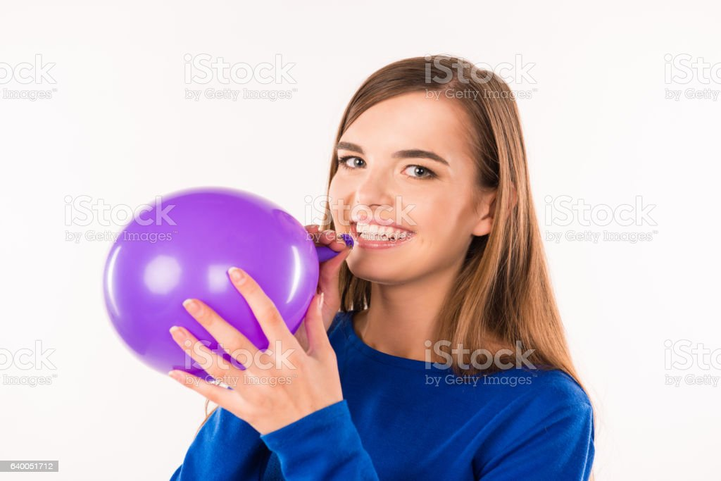 cute smiling young woman blowing violet balloon stock photo