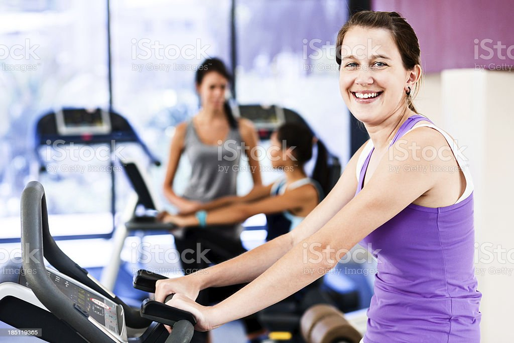 Cute smiling young woman uses exercise bike in gymnasium stock photo