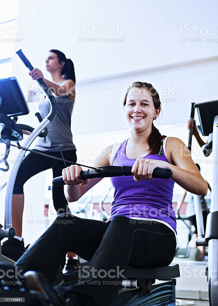 Cute smiling young woman using rowing machine in gym stock photo