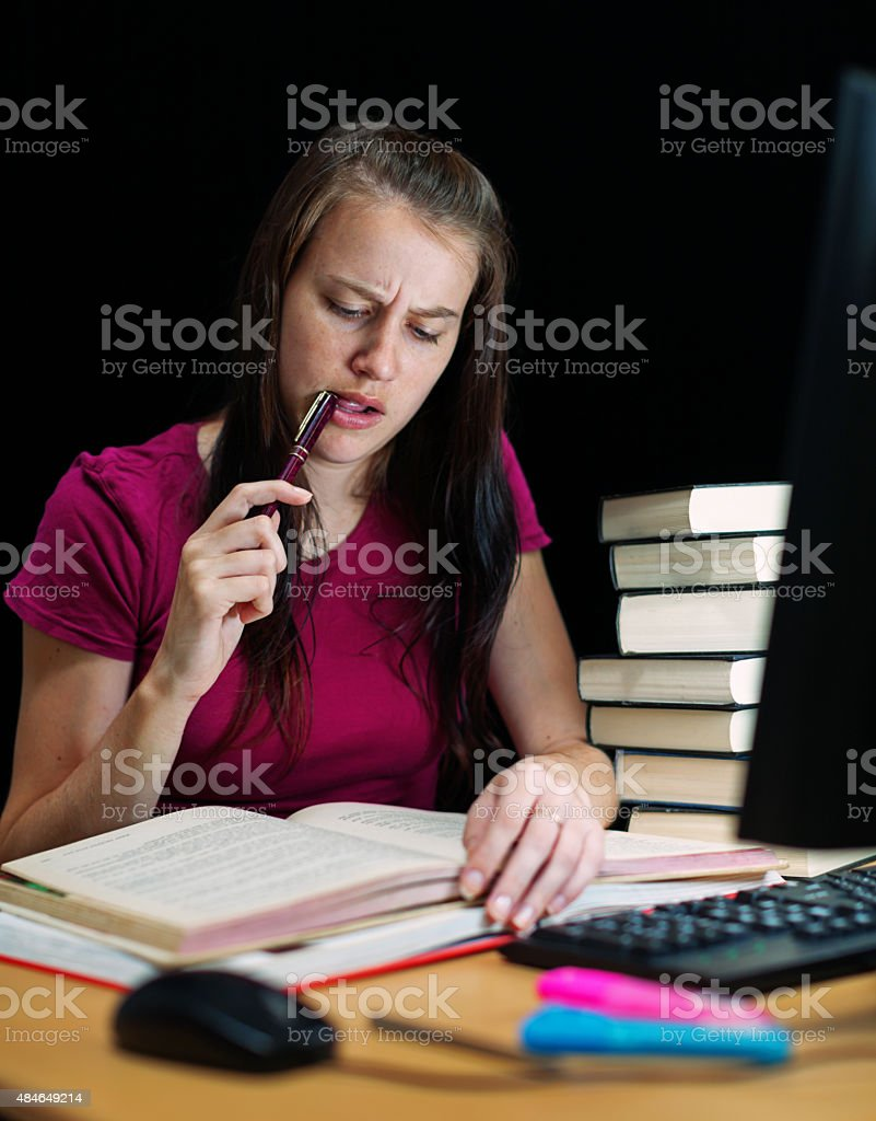 Cute student frowns, chewing her pen, concentrating on her studies stock photo