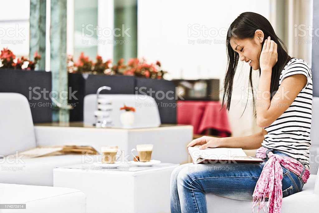 Cute student girl reading in a restaurant royalty-free stock photo