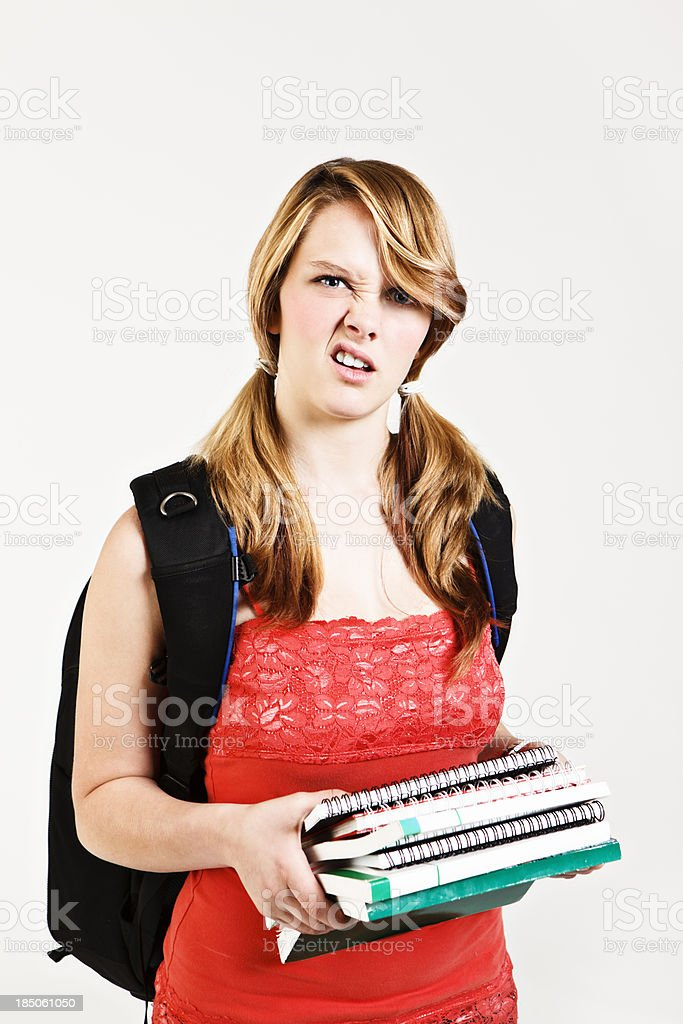 Cute student looks confused about books she carries stock photo