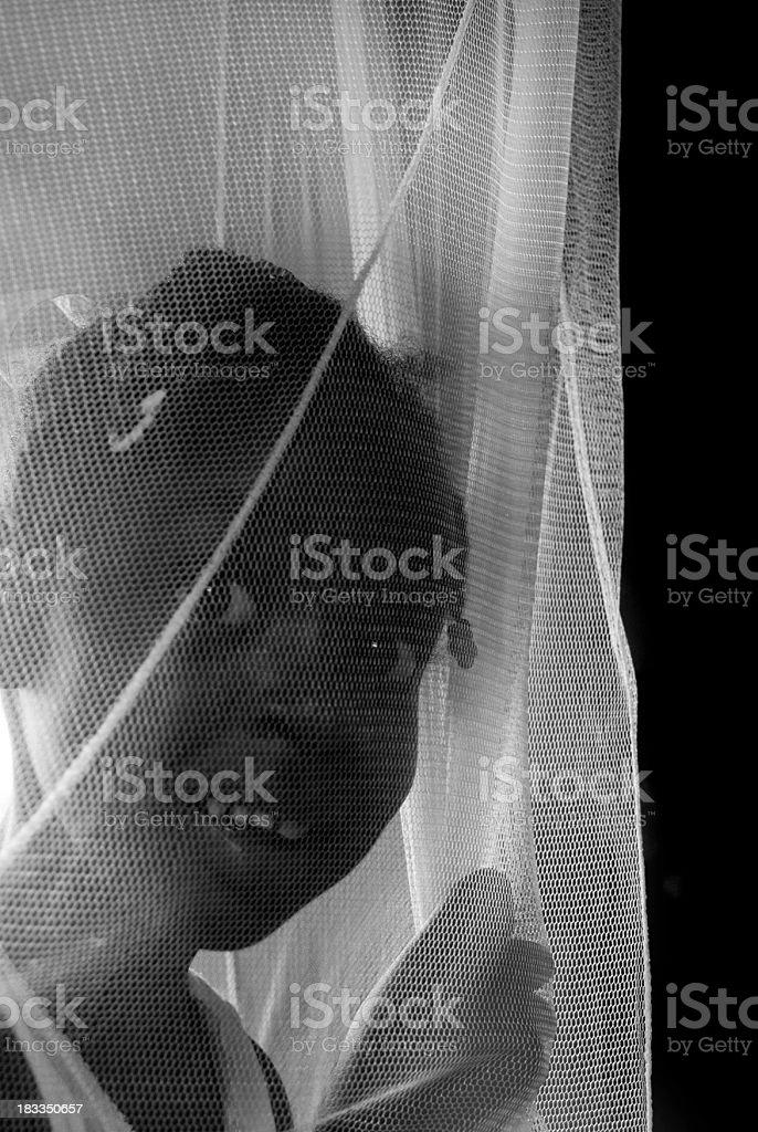 cute surprised black girl behind netting material stock photo