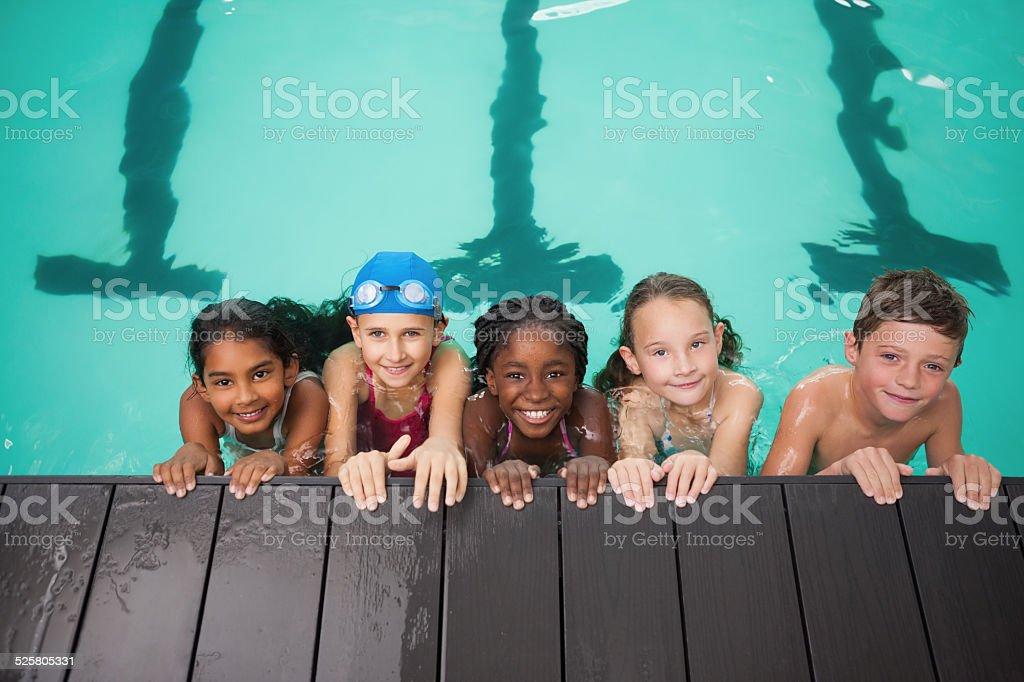 Cute swimming class smiling at camera stock photo