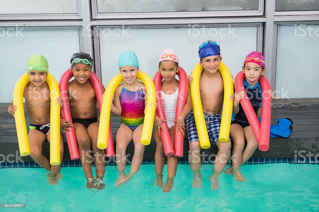 Cute swimming class smiling poolside stock photo